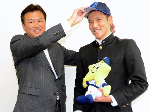 写真:堀井恒雄専任部長からベイスターズの帽子をかぶせてもらう北方投手=唐津商