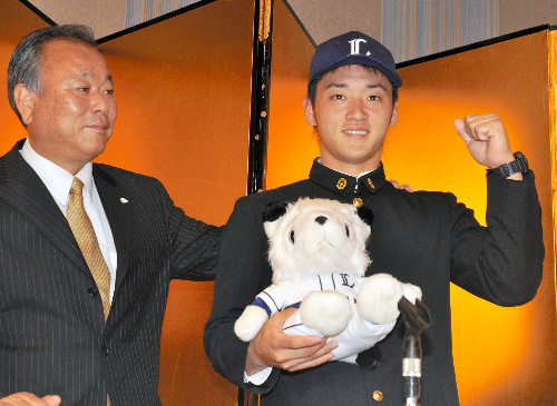 写真:西武の帽子をかぶってガッツポーズをする永江恭平選手(右)と奥薗満編成部長=長崎市大黒町のホテル