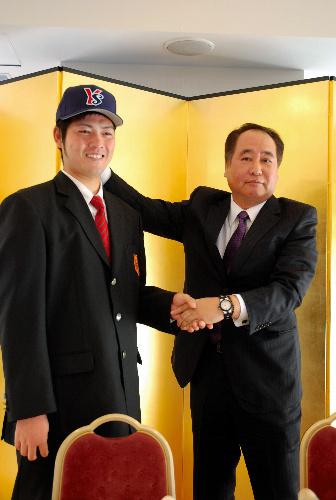 写真:仮契約後、握手を交わす木谷良平投手(左)と鳥原公二・球団チーフスカウト=大分市