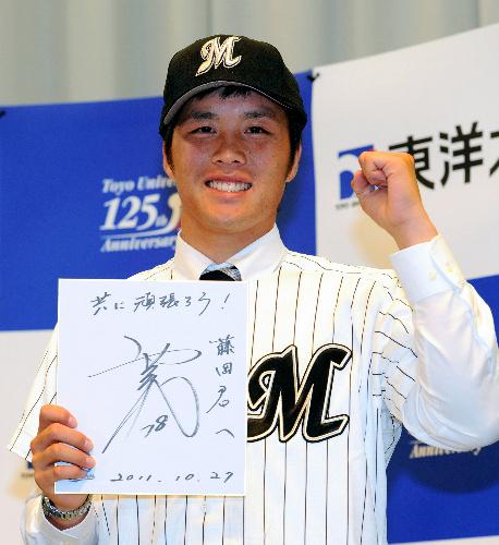 写真:ロッテから1位指名を受けて、西村監督の色紙を手に笑顔を見せる東洋大の藤岡貴裕投手=山本裕之撮影