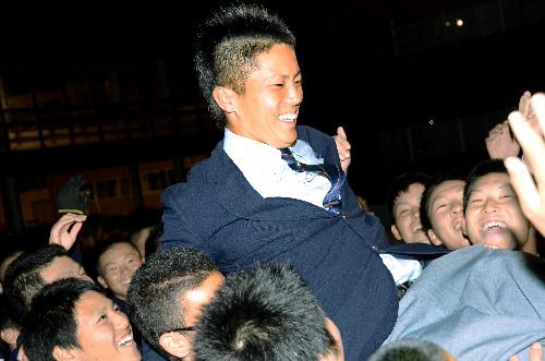 写真:野球部のメンバーに胴上げされる川上竜平選手=八戸市の光星学院高
