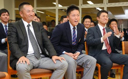 写真:1位指名が発表された瞬間、テレビ画面を見つめる川上竜平選手(中央)。左は仲井宗基監督=八戸市の光星学院高