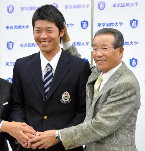 写真:古葉監督に祝福される伊藤投手(左)=東京都新宿区