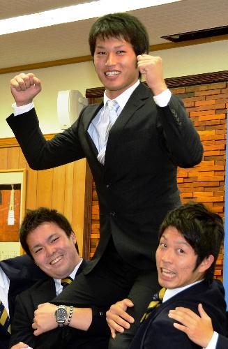 写真:仲間に担がれ、ガッツポーズする中根投手(中央)=仙台市青葉区