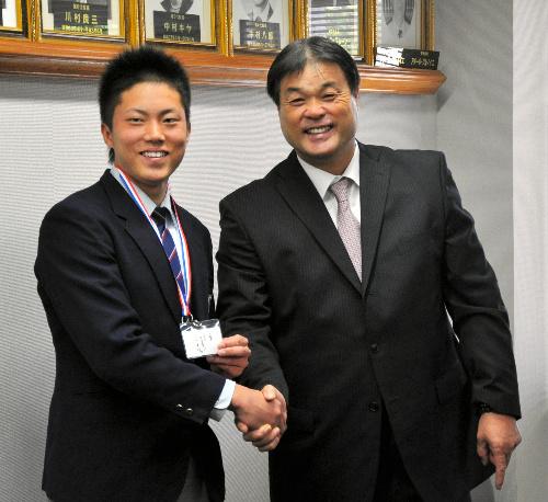 写真:握手を交わす川上竜平選手(左)とヤクルトの渡辺進・球団編成部長=31日、八戸市の光星学院高