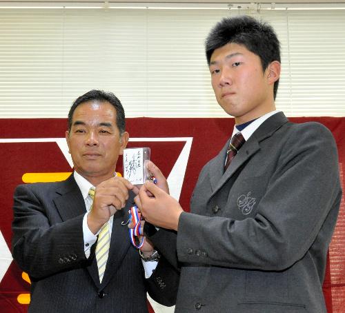 写真:中尾スカウトから和田監督のサイン入りパスを受け取る歳内投手=伊達市の聖光学院