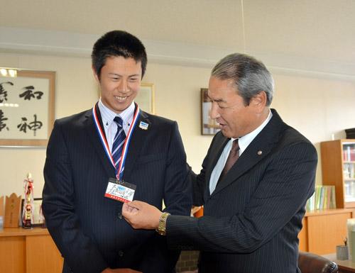 写真:中田スカウト部長から渡されたドラフト会議場パスを首にかけ、談笑する川崎投手(左)