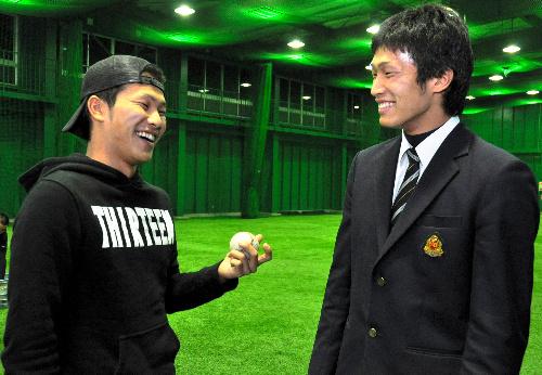 写真:日本文理高の室内練習場で談笑する高橋洸内野手(右)と兄の潤さん=新潟市西区新通