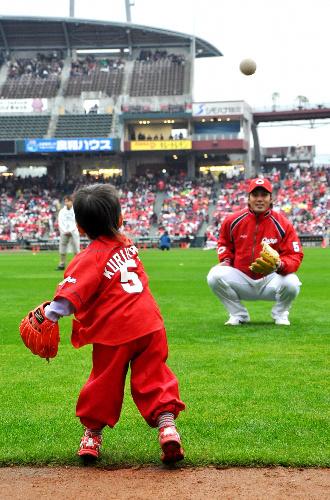 写真:子どもとキャッチボールする栗原健太選手(右)=広島市南区のマツダスタジアム