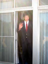 写真:寮の自室の窓から手を振る菊池は「高校の寮より大きいです」