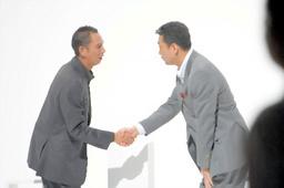 写真:2007年9月、テレビCMで共演した江川氏と握手する小林繁さん(左)