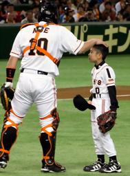 写真:亡くなった巨人・木村拓也コーチの長男、恒希くんは、始球式で阿部慎之助捕手に頭をなでられる=24日、東京ドーム、長島一浩撮影