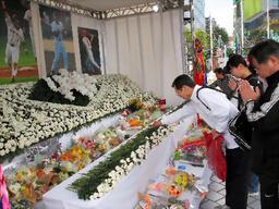 写真:故木村コーチの献花台の前で手を合わせるファンら