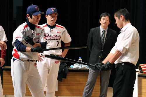 写真:ヤクルト・飯原誉士選手(左端)、田中浩康選手(左から2番目)からバッティングの指導を受ける高校生=11日、県文化センター