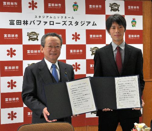 写真:協定書を手に笑顔を見せる多田・富田林市長(左)とオリックスの前田投手(右)=富田林市常盤町の富田林市役所