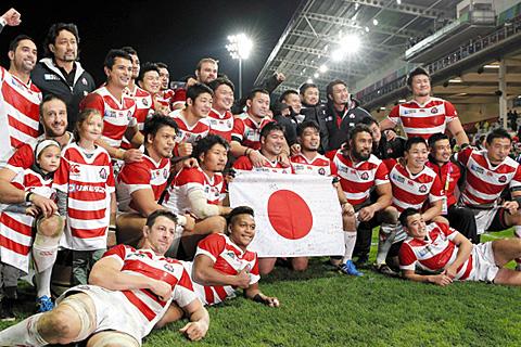 W杯初の1大会3勝を挙げて喜ぶ日本代表の選手たち=AFP時事