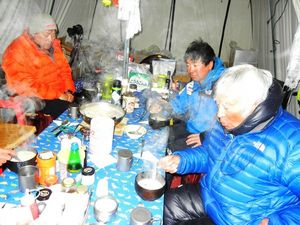 16日、アタック開始前の三浦隊テントで、雑炊を食べる三浦雄一郎さん(手前)、次男の豪太さん(右上)、長男の雄大さん(左上)