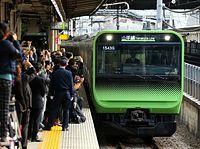 初乗りをめざす大勢のファンらが待つ中、大崎駅に入線する山手線の新型車両E235系=30日午後、東京都品川区、林敏行撮影