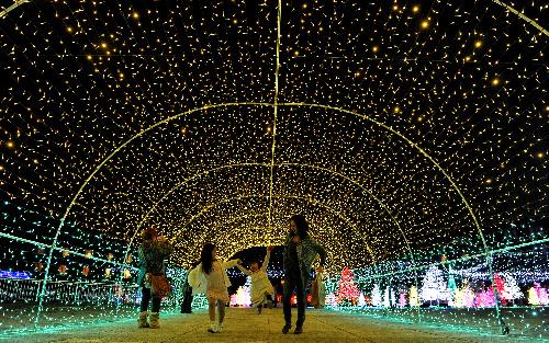 写真:光り輝くイルミネーションの中を歩く人たち=1日夜、神戸市北区、諫山卓弥撮影