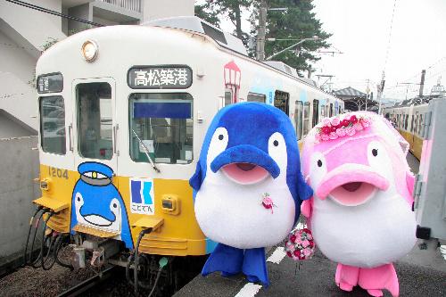 写真:開業100周年記念のラッピング電車と挙式したことちゃん(左)、ことみちゃん=香川県琴平町