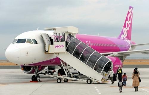 写真:就航1年を迎えたピーチ・アビエーションの機体に、乗客たちが次々に乗り込んだ=1日午前、関西空港
