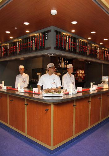写真:カウンターに職人が立つすし店。カウンターの下には荷物をかけられるフックがついている=15日、羽田空港