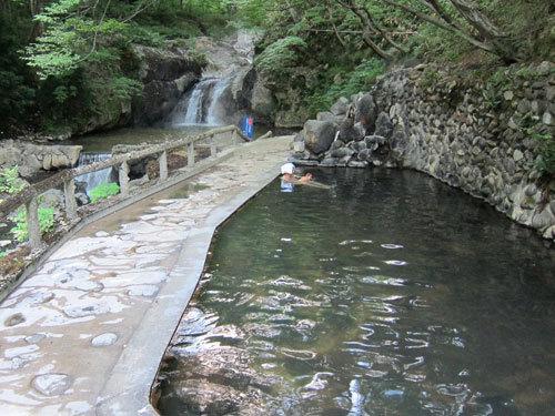 写真:渓流沿いの木々に囲まれた露天風呂。その奥の滝つぼは天然の温泉になっているが、熱くて入れなかった