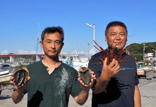 写真:島で取れた伊勢エビやアワビを手にする甲田豊さん(左)と石橋英樹さん=横尾写す