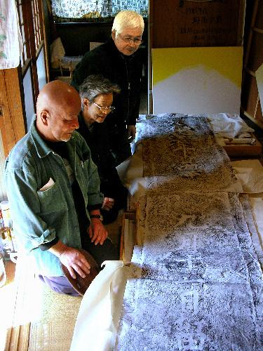 写真:西田橋の要石の拓本と、石原正信さん、森山愛子さん、野ぞえ宗男さん(奥から)=根岸写す