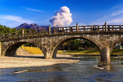 写真:移設された西田橋。後方で桜島が噴煙を上げる=上田頴人撮影