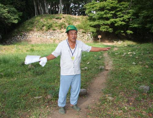 写真:小谷城跡を説明する中山孫孝さん。後方は本丸跡の石垣