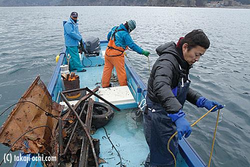 写真:漁協で船を出してもらい、船上から引き上げ作業を行なうボランティア。海中ガレキ撤去作業は、このように、水中班と引き上げ班に別れて、行なわれている
