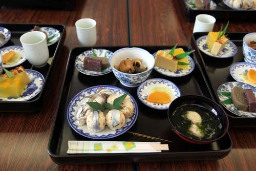 写真:昼食は、新上五島町奈良尾郷の郷土料理研究会の方々が、一週間も前から準備してくれた「紀寿し」「おかめ寿司」(写真手前左の皿の上にある)などの伝統的手作り料理。その美味しさは参加者に深い感銘を与えた