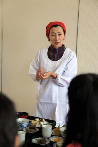 写真:郷土料理研究会会長の谷佳江さんが、一つ一つの料理を丁寧に説明してくださった。同会が旅行者に食事を提供したのは初めてだという