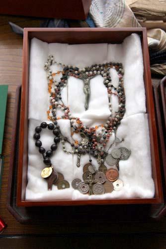 写真:先祖伝来のロザリオと奉納された硬貨