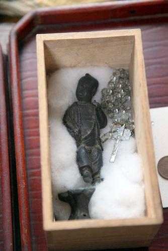 写真:イエス・キリスト像と伝わる「神様」とロザリオ。箱の中には、江戸時代に奉納されたと思われる古銭も数枚入っていた