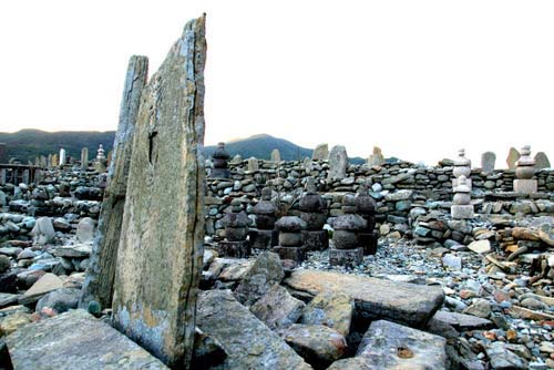 写真:日島曲古墳群。五島列島を拠点に、日本本土、朝鮮半島、中国大陸を繋ぐ海上交易ネットワークを築き上げた14〜15世紀の前期倭冦の墓碑群。背後には、生前の彼らが活躍した大海原が広がっていた