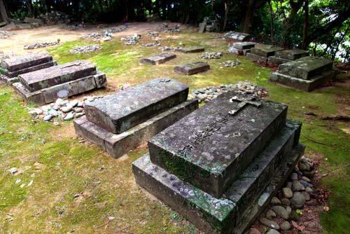 写真:旧五輪教会近くにある五輪墓地。左右に並んだ西洋的カマボコ型(伏碑型)墓碑、丸石を重ねた配石墓、そして、左奥には、子孫の都市部への引っ越しに伴い、骨が上げられたのち、捨て置かれた墓碑群が見える