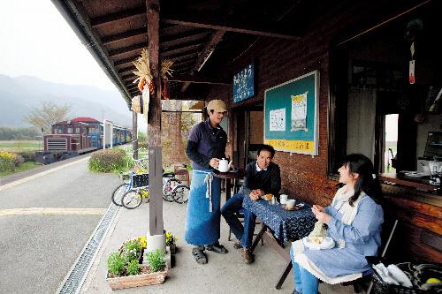 写真:ホームでお客さんと話す久永さん(左)。トロッコ列車が走り込む=比田勝大直撮影