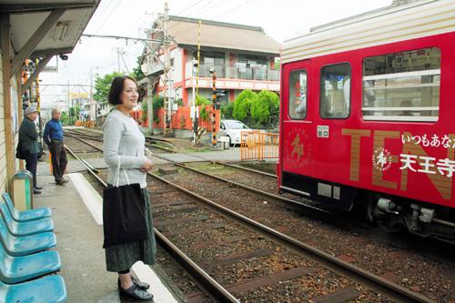 写真:神社の社殿(踏切の奥)と隣り合わせの高須神社停留場。安井寿磨子さんは今も週3回はチンチン電車に乗る=塚原紘撮影