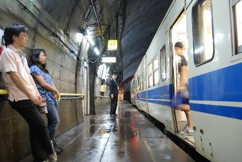 写真:電車を出迎える小田嶋嘉秋さん(中央)。ホームは湿ったにおいがする=馬田広亘撮影