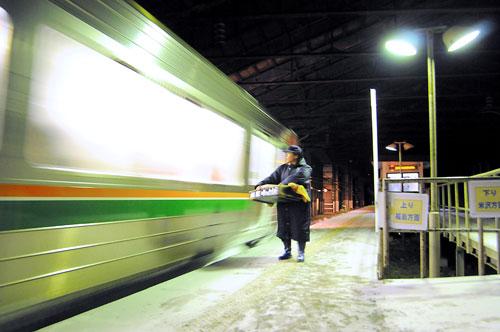 写真:「峠の力餅」を抱えた小杉敏子さんの前に列車が入ってきた=馬田広亘撮影