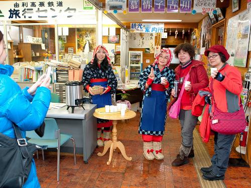 写真:台湾から来た団体客と記念撮影する佐藤まつ子さん(右から3人目)。かすりの着物の「おばこ姿」と陽気さで人気者だった=松岡誠太朗撮影