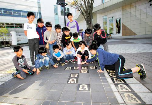 写真:天童駅前広場で詰将棋に興じる「天童少年少女将棋教室」の子どもたち。地面に描かれた詰将棋は市内19カ所にある=鈴木愛子撮影