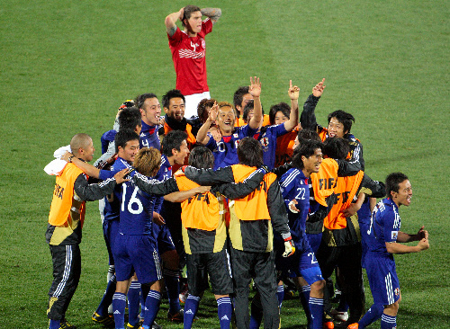 写真:デンマークを破って決勝トーナメント進出を決め、集まって喜ぶ日本代表の選手たち=西畑志朗撮影