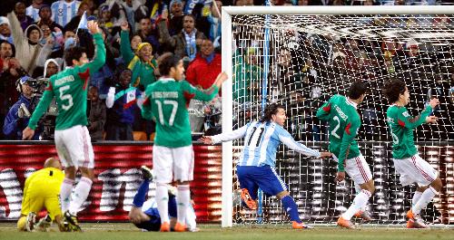 写真:前半26分、先制ゴールを決めたアルゼンチンのテベス(11)(中央)と、オフサイドを主張するオソリオ(5)、ドスサントス(17)らメキシコの選手たち=AP