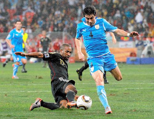 写真:前半、ゴール前に抜け出したドイツ・カカウ(19)のボールを奪うウルグアイのフシレ(4)=杉本康弘撮影