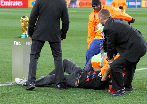 写真:ワールドカップに触ろうとピッチに乱入し、取り押さえられた観客=越田省吾撮影