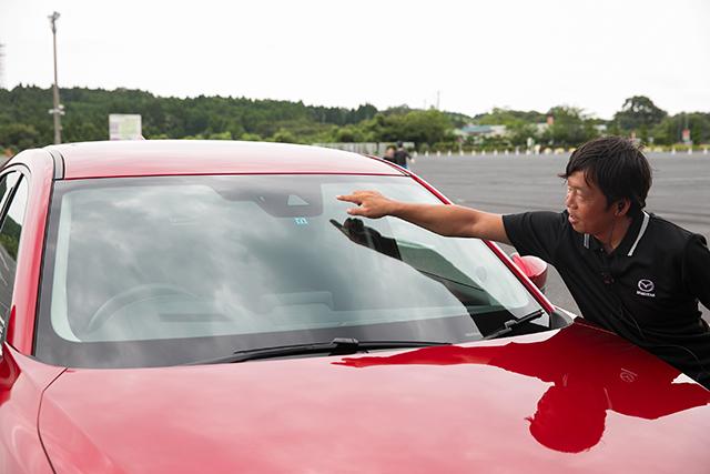 自動ブレーキとAT誤発進抑制制御について説明してくれた内海さん。誤発進はこのフロントガラス上部のカメラと、ナンバープレート横にあるソナーで判断している