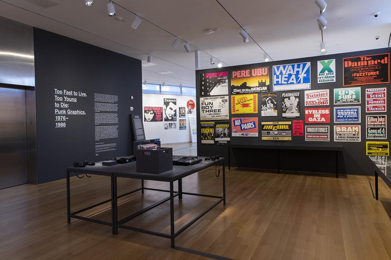 中央のテーブルにパンク・ロックのレコードとターンテーブルが置いてあり、視聴することができる。 Installation view of Too Fast to Live, Too Young to Die: Punk Graphics, 1976-1986 at the Museum of Arts and Design, New York (April 9–August 18, 2019). Photo by Jenna Bascom